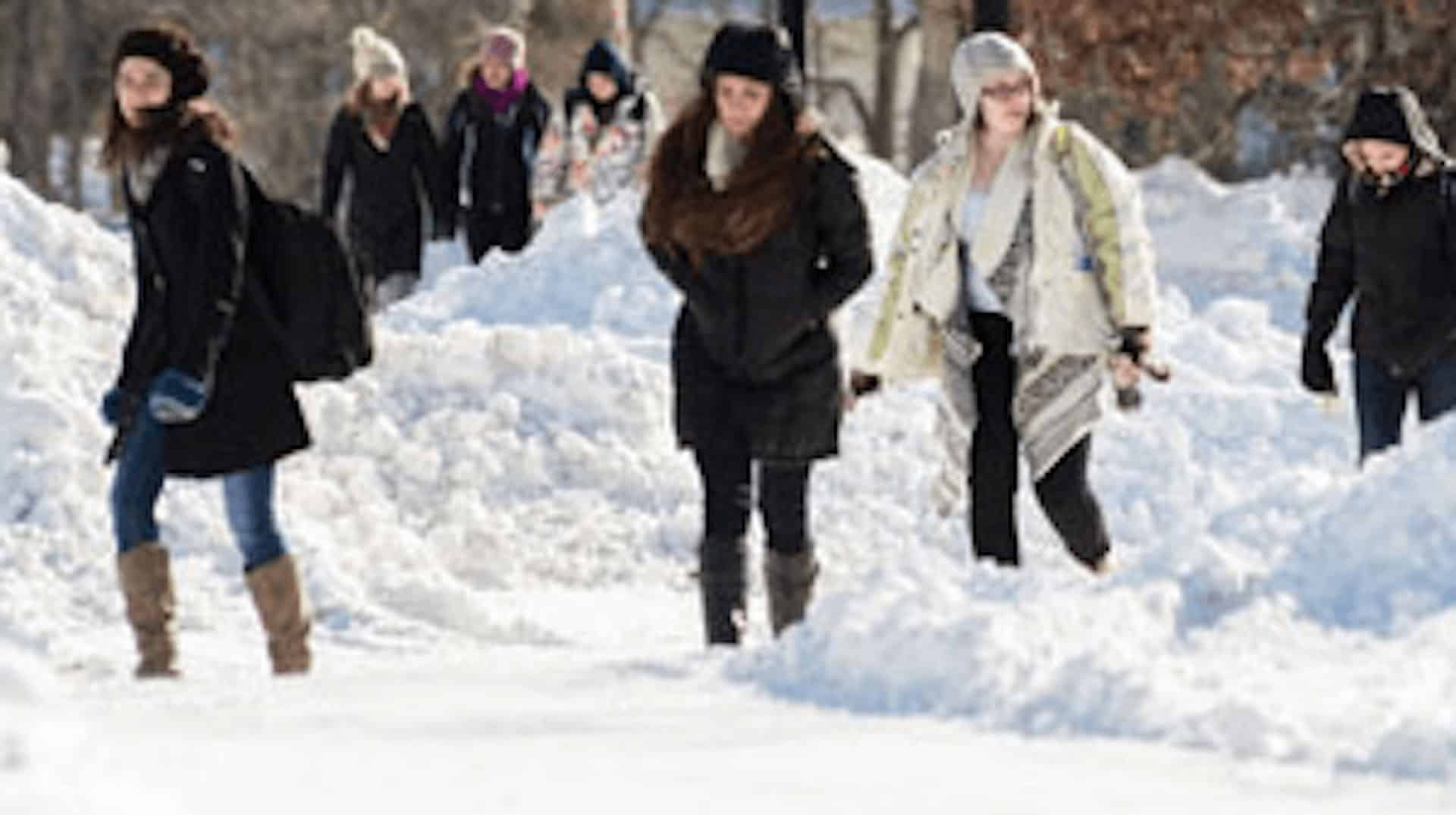 Students in winter coats walking through the snow to class.