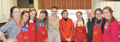 Chi Omega group photo in baking aprons with Dr. and Mrs. Arnn.