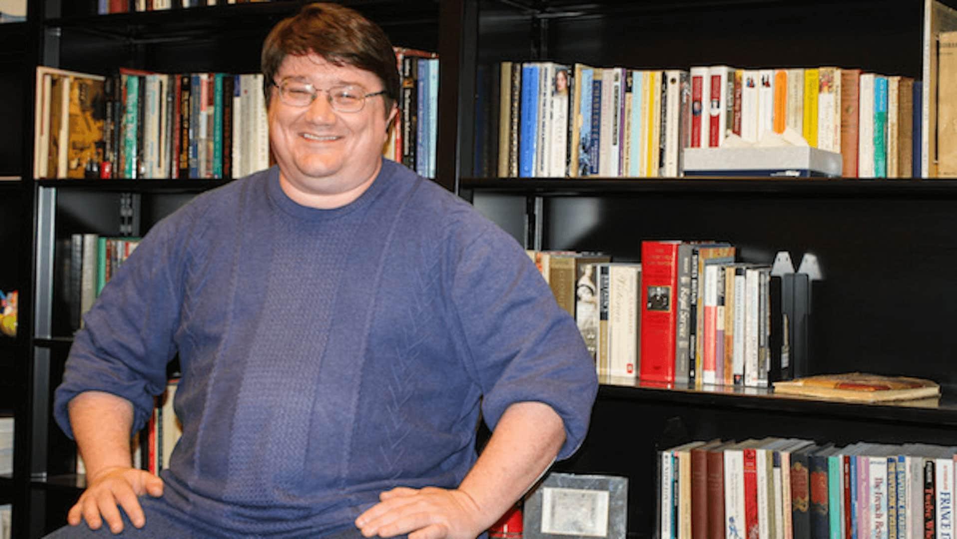 Dr. David Stewart in front of bookshelves.