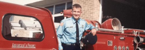 Erik Prince standing in front of a firetruck.