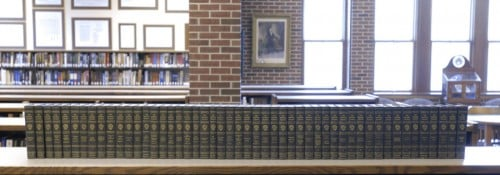 A large book collection sitting on a shelf in the Hillsdale College library.