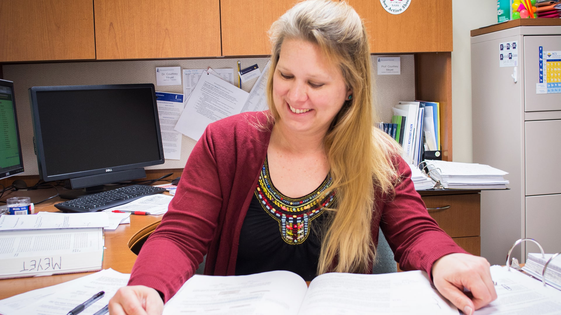 Dr. Courtney Meyet examines student research papers in her office