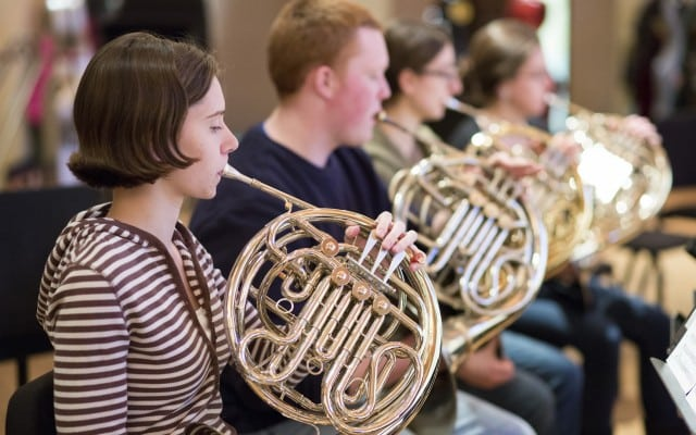 French horn section at orchestra rehearsal.