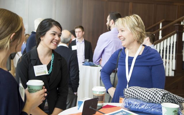 Several individuals conversing at a Career outreach meet-and-greet.