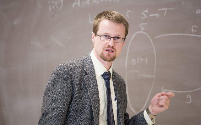 Dr. Gaebler in front of a blackboard, teaching class.