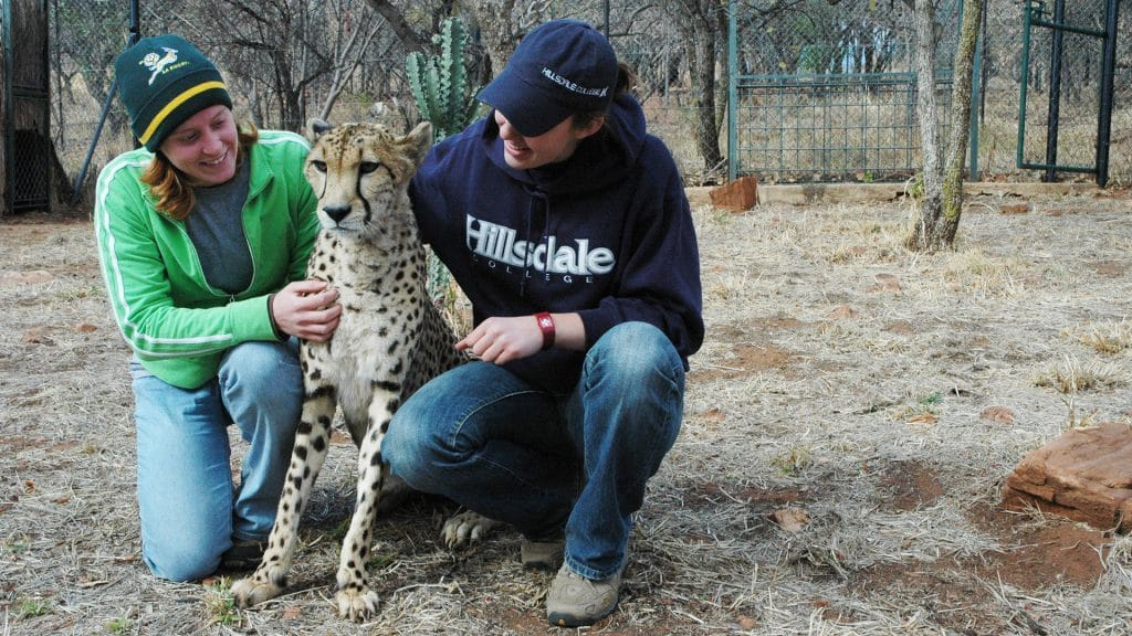 Two students posing with a cheetah.