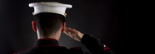 A U.S. Marine saluting against a black background while in the dress blues service uniform.
