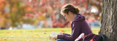 Student reading book outside on campus