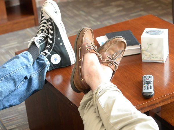 A couple resting their feet on a coffee table, relaxing.