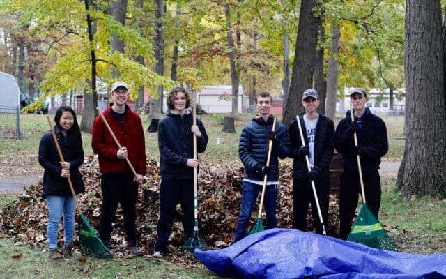 """""""A Few Good Men"""" volunteers raking leaves."""