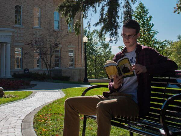 Student reading a book on a bench on campus.