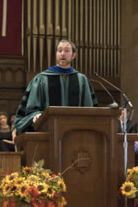 Adam Carrington in doctoral robes giving a speech at commencement.