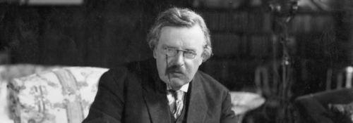 G. K. Chesterton writing at his desk.