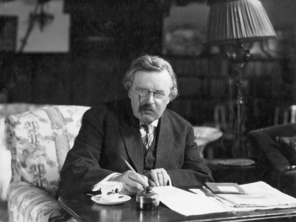 G. K. Chesterton writing at his desk.