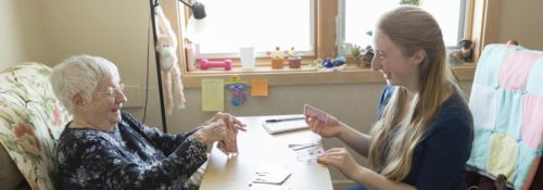 Hillsdale student playing cards with residents of an assisted living facility.