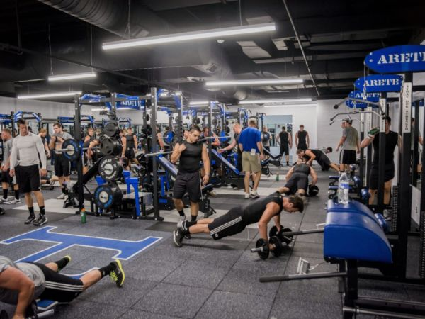 Student athletes exercising in the sports weight room.