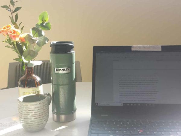 Thermos of tea and a laptop open for editing essays.