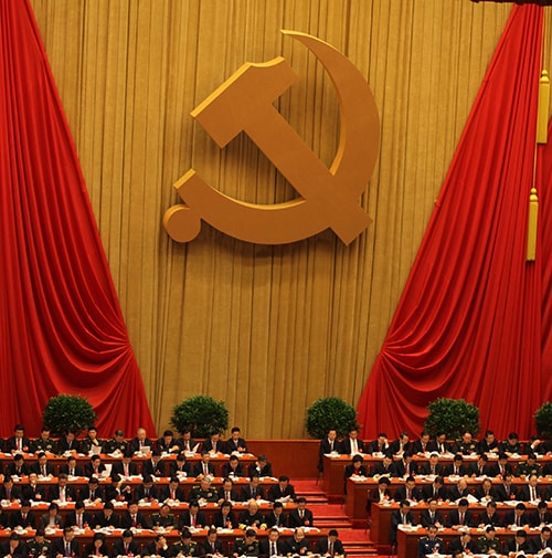 Rows of seated Chinese politicians with the Hammer and Sickle displayed on the back wall.