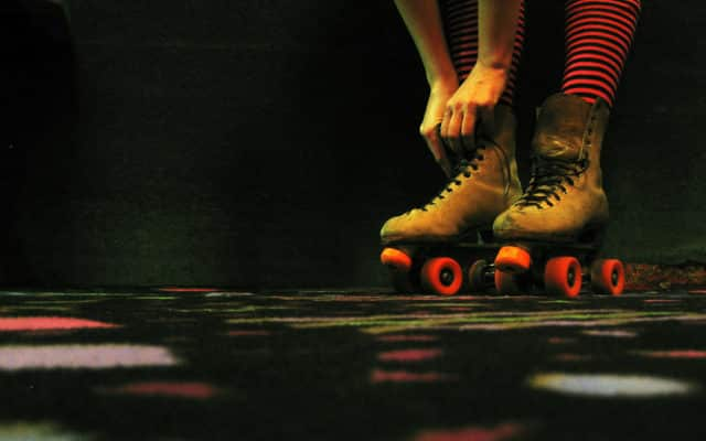 A woman tying her roller skate laces.
