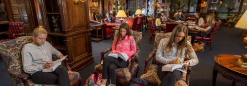 Three students studying in the Heritage room of the Hillsdale College Library..