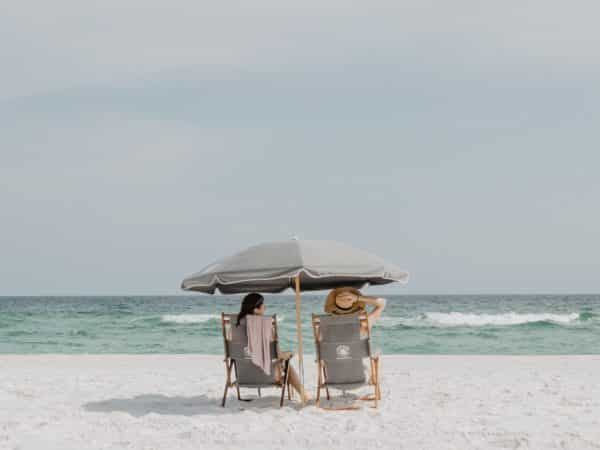 Two women sitting under a canopy on the beach.
