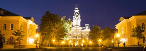 Wide view of Hillsdale College Central Hall at night with sidewalk lamps on.