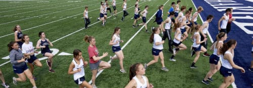 Hillsdale Track team running on the football field during practice.