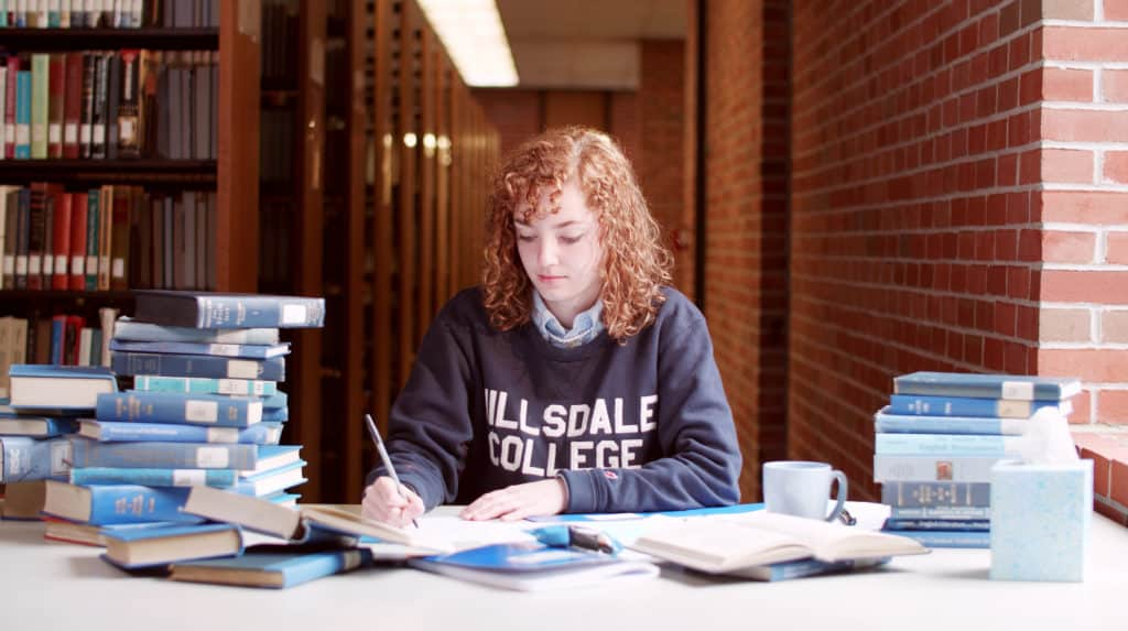 Hillsdale College student writing in the library, surrounded by blue books.