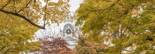 Hillsdale College clock tower through autumn trees