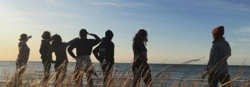 Students on beach at sunset