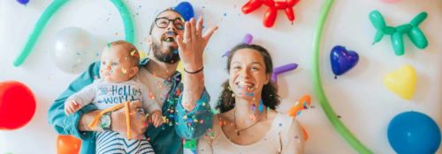 Parents celebrate in front of a bright, colorful background of shaped balloons