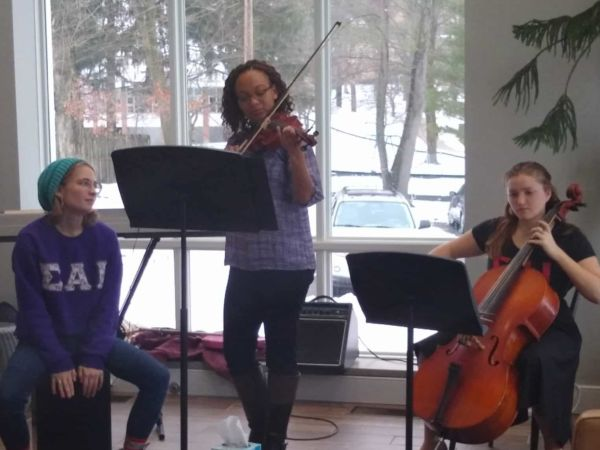 Three female students play instruments for a small audience