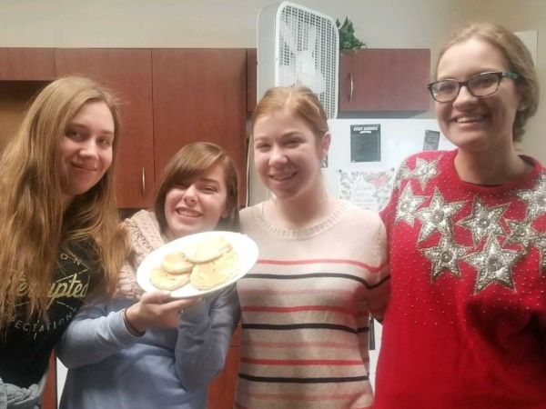 Four female students stand in a dorm kitchen with a plate of homemade tortillas
