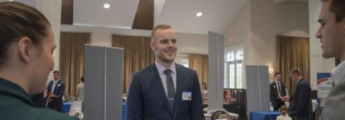 Student speaking with two others at classical school job fair