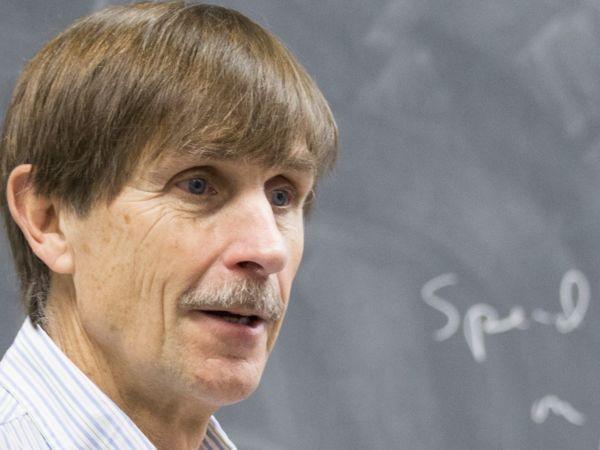 Economics Professor Gary Wolfram standing in front of a blackboard