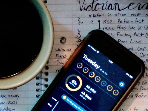 Photo of a coffee cup and phone with sleep app open, sitting on a page of student's notes