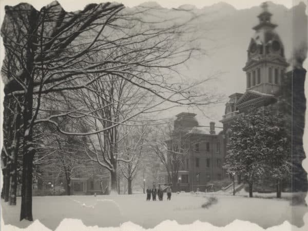 An old photograph of Central Hall in the snow with students standing nearby