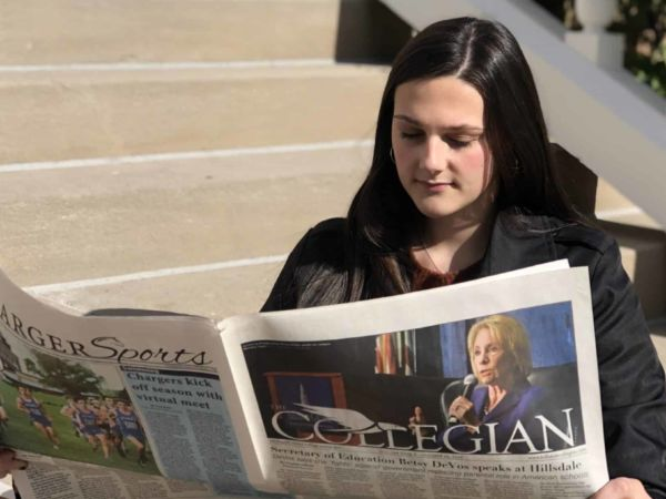 Students sits on Central Hall front steps, reading The Collegian