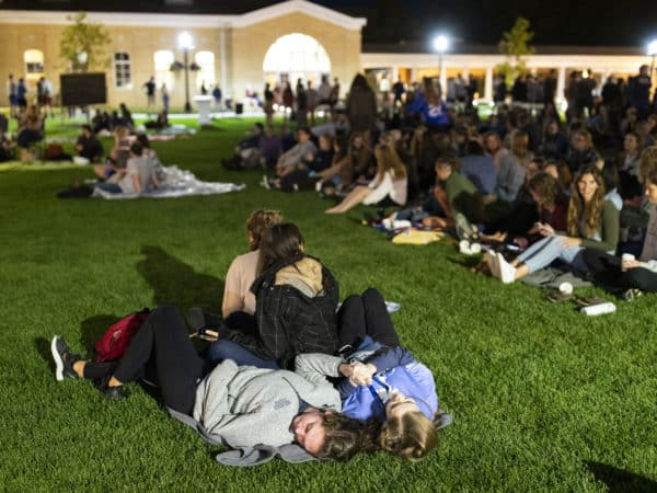 students lay on a blanket on the middle of a grassy quad at night