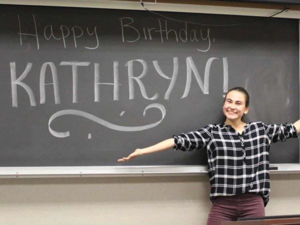 "Female student stands smiling in front of a blackboard that reads ""Happy Birthday, Kathryn!"""