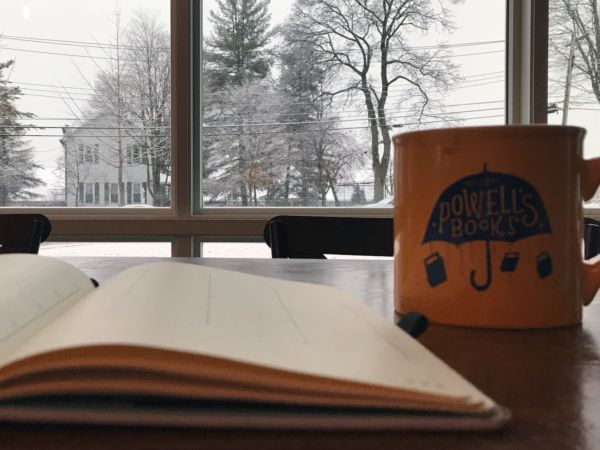 A book and a mug sitting on a table in front of a window overlooking a snowy day