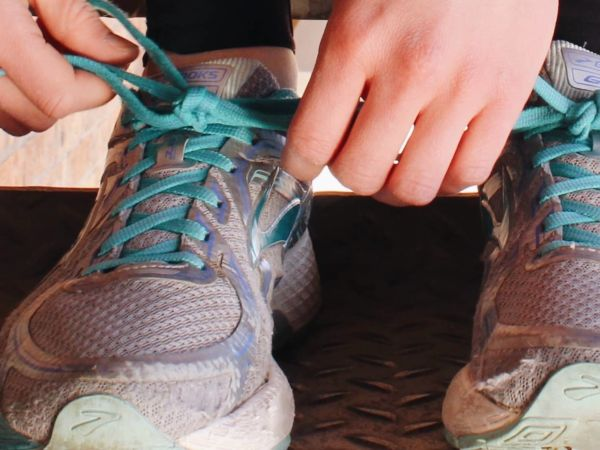 running shoes with two hands tying one shoe