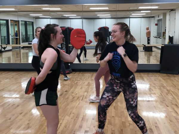 Two women in a gym studio holding targets and wearing boxing gloves
