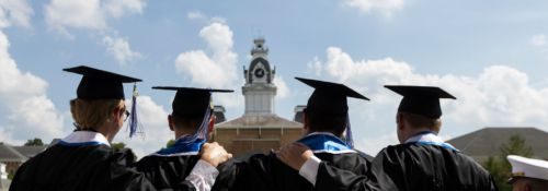 graduating students facing clocktower with blue skies