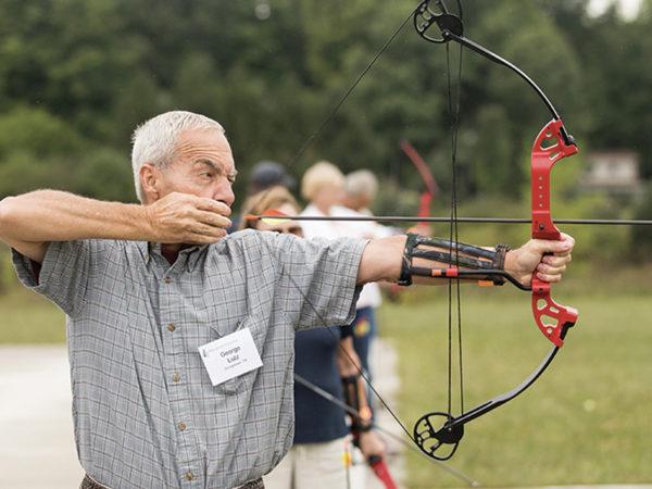 An event participant aims a bow.
