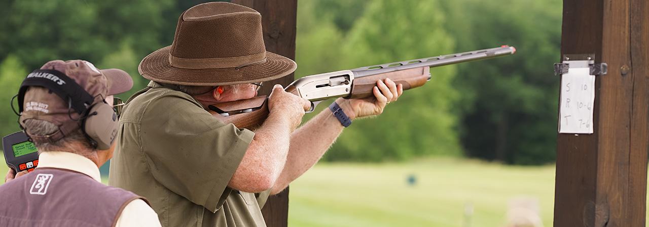 A participant aims a rifle at a clay pigeon.